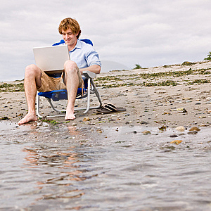 Man with laptop on beach.